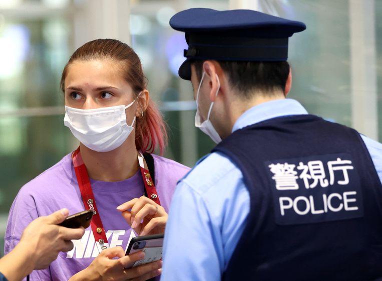 Kristina Tsimanoeskaja spreekt met de Japanse politie op de internationale luchthaven van Tokio. (01/08/2021) Beeld REUTERS