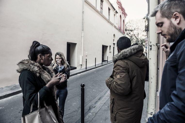 Leerlingen van de Ecole de Commerce namen al snel weer hun vertrouwde rookplekje voor de deuren van Le Bataclan in. Gewoonten sterven minder snel dan mensen. Beeld Karoly Effenberger