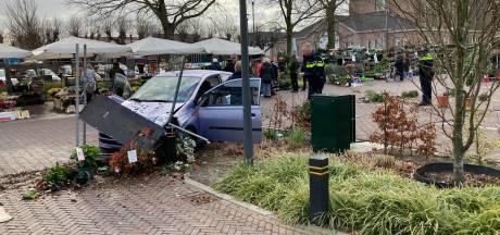 Auto rijdt dwars door kraam van bloemenverkoper
