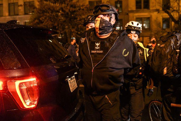 Een lid van de Proud Boys wordt opgepakt. Beeld AFP