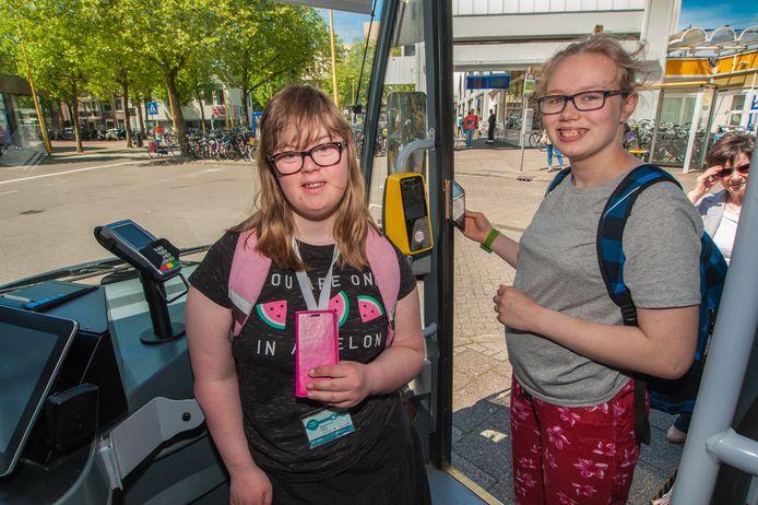 Eva Renes (17) en  Tanja Glebbeek (15) uit Gouda stappen in de bus. Met behulp van een speciale ov-app kunnen de leerlingen, die bij De Ark speciaal onderwijs volgen, zelfstandig met de bus reizen.