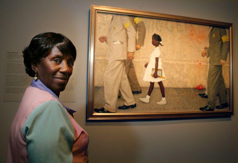 Lucille Bridges poseert naast het schilderij van Norman Rockwell 'The Problem We All Live With'. Beeld AP
