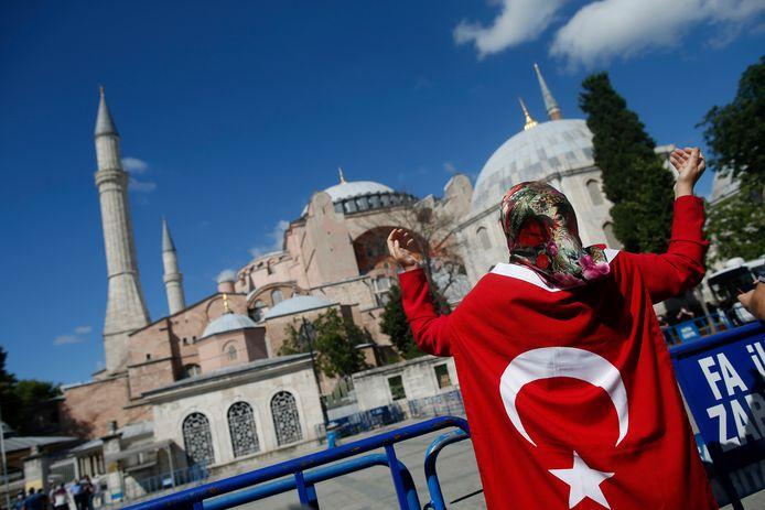 Een vrouw gehuld in een Turkse vlag voor de Hagia Sophia in Istanboel.