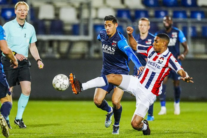 Driess Saddiki (rechts) trapt de bal weg voor AZ-speler Tijjani Reijnders.