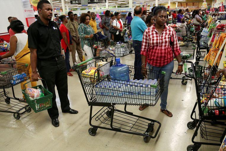 Aanschuiven geblazen in Jamaicaanse supermarkten, waar de bewoners massaal een voorraad inslaan voor de komst van orkaan Matthew. Beeld REUTERS
