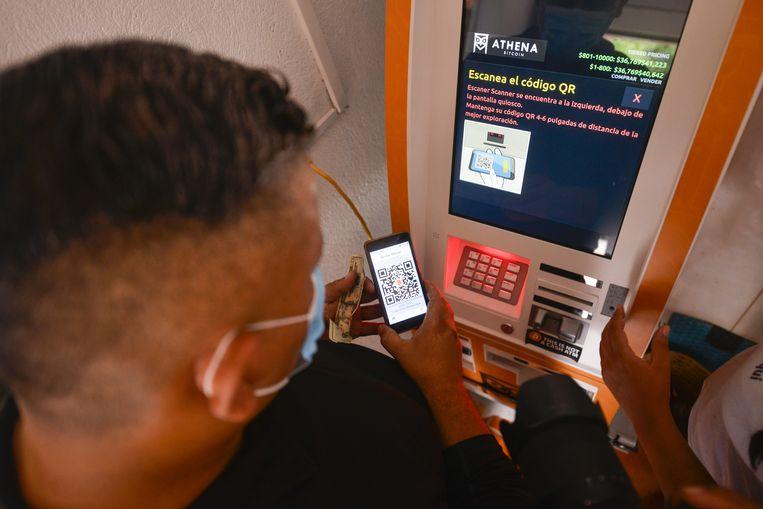 Een man scant een QR-code op de enige bitcoinautomaat in  El Zonte, El Salvador.  Beeld Alex Pena / Anadolu / Getty