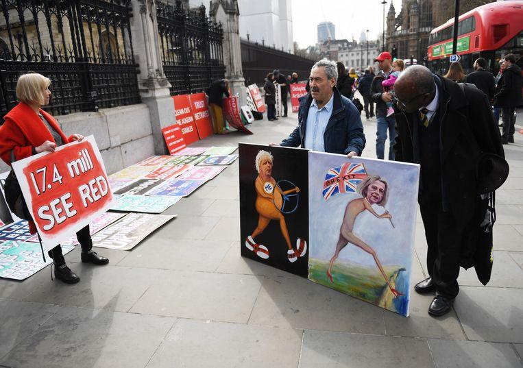 De Londense kunstenaar Kaya Mar toont zijn schilderijen buiten aan het Britse parlement. Beeld EPA