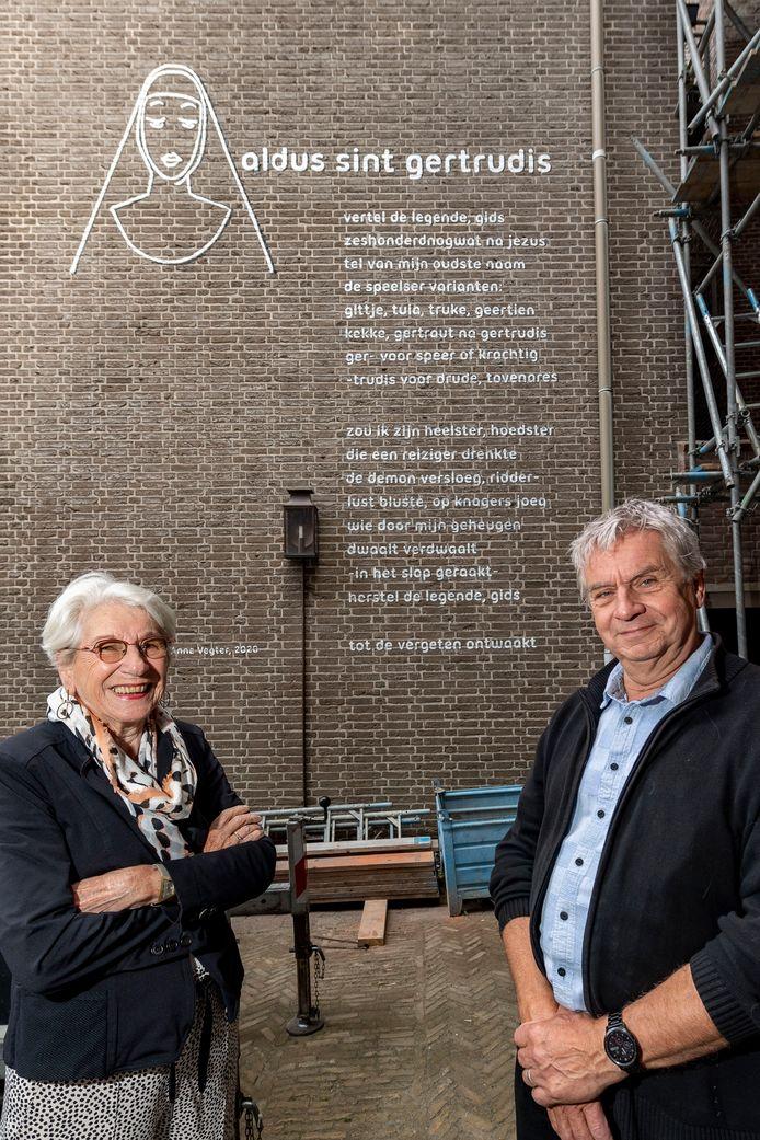 Ies Telkamp (vrijwilliger) en Ad Segers (voorzitter) van De Bergse stadsgidsen (SBM) bij het muurgedicht van Anne Vegter ter gelegenheid van het 25 jarig bestaan van SBM.