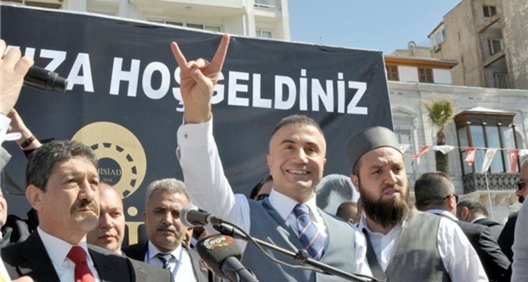 Sedat Peker maakt het gebaar van de Grijze Wolven voor een affiche van Misiad en naast de algemeen directeur van Misiad. Beeld rv