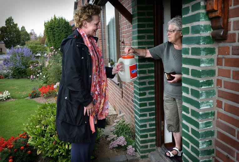 Een collectant gaat langs de deuren voor KWF. Beeld null