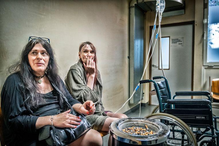 Nashota (l) en Jenny, haar transvrouw in de rookruimte van het ziekenhuis van Sint-Niklaas: 'Jenny heeft niet veel longcapaciteit meer, maar dat heeft niets met haar rookgewoonten te maken.' Beeld Tim Dirven
