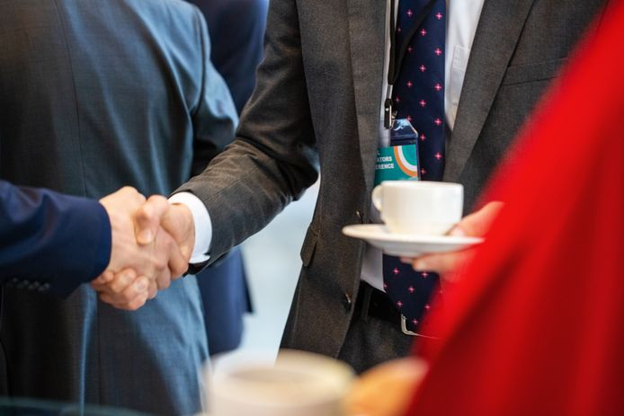 Business executives shaking hands in coffee break. Business people taking coffee break during a conference.