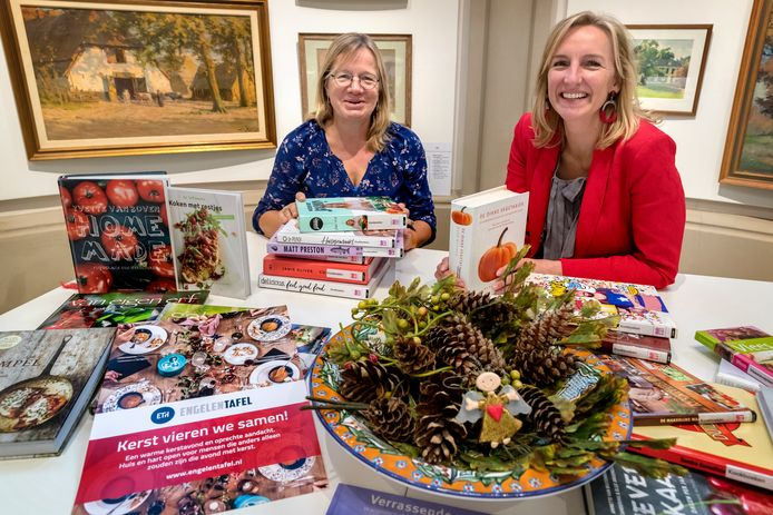 Marianne Bax uit Schijndel (l) en Jeannette Saatrube uit Vught zoeken in de bibliotheek naar geschikte kookboeken voor een kerstmaaltijd waarbij zij thuis vreemde alleenstaanden ontvangen.