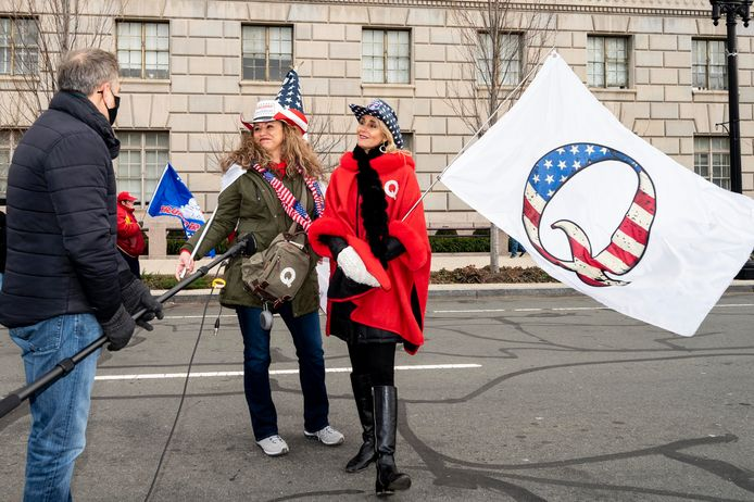 Een aanhangster van complotbeweging QAnon met bijhorende vlag. De twee demonstranten waren op 6 januari (foto) aanwezig op de pro-Trump-massademonstratie die uitmondde in de Capitoolbestorming.