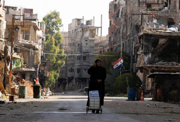 Een vrouw loopt door de verwoeste straten van de Syrische hoofdstad Damascus. Beeld Reuters