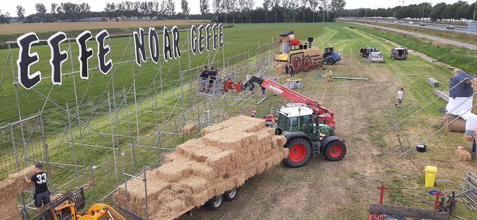 Vrijwilligers van Effe noar Geffe werken zaterdag aan het traditionele stropoppendorp, pal naast snelweg A59.