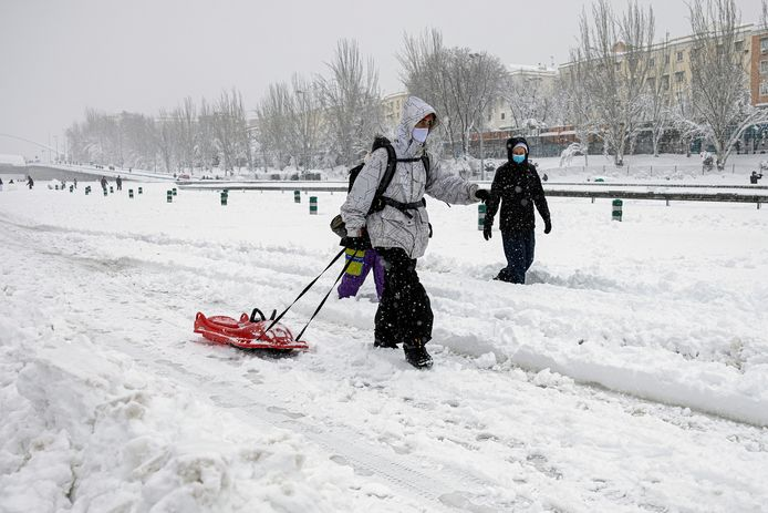 epa08928119 A couple walks along the M30 ring road covered in a thick layer of snow in Madrid, Spain, 09 January 2021. Storm Filomena brought the heaviest snowfall in decades.  EPA/Rodrigo Jimenez