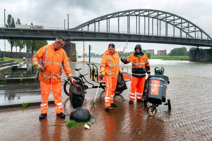 Een ochtendploeg van De Brug in actie bij de John Frostbrug in Arnhem. Links begeleider Kees Nijdam, rechts daarvan deelnemers Jan en Cees.