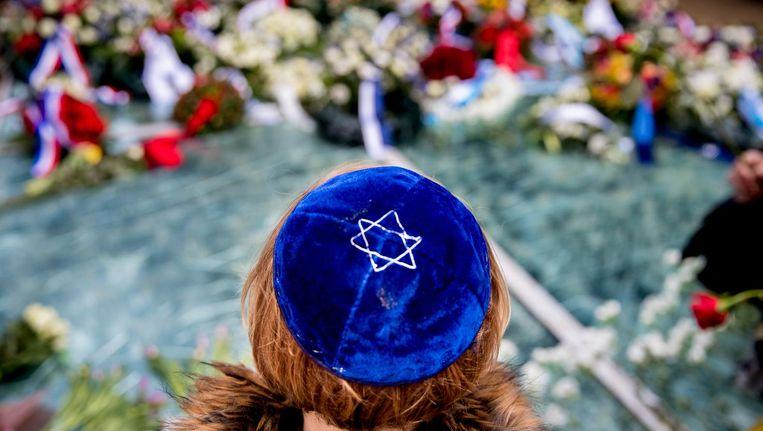 Mensen leggen bloemen bij het Spiegelmonument tijdens de Nationale Holocaust Herdenking. Beeld anp