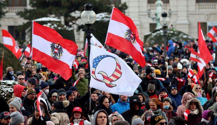Ook in Oostenrijk duikt QAnon op. Een betoger zwaait met een vlag van de complottheorie tijdens een betoging in Wenen op 16 januari.