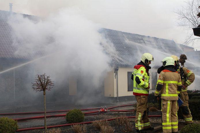 De brandweerlieden in overleg terwijl collega's het vuur doven.
