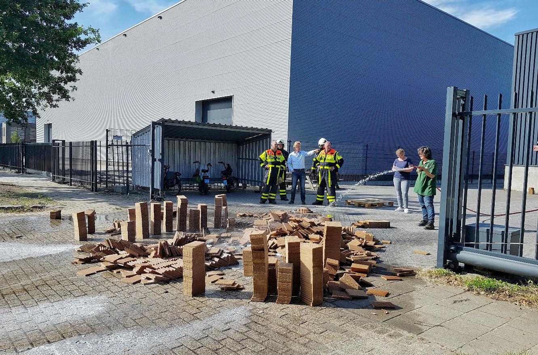 Weer brand bij aanmaakblokjesfabriek in Oisterwijk. Kees van Opstal, eigenaar van Fire Up, kijkt samen met brandweerlieden naar het laatste bluswerk.