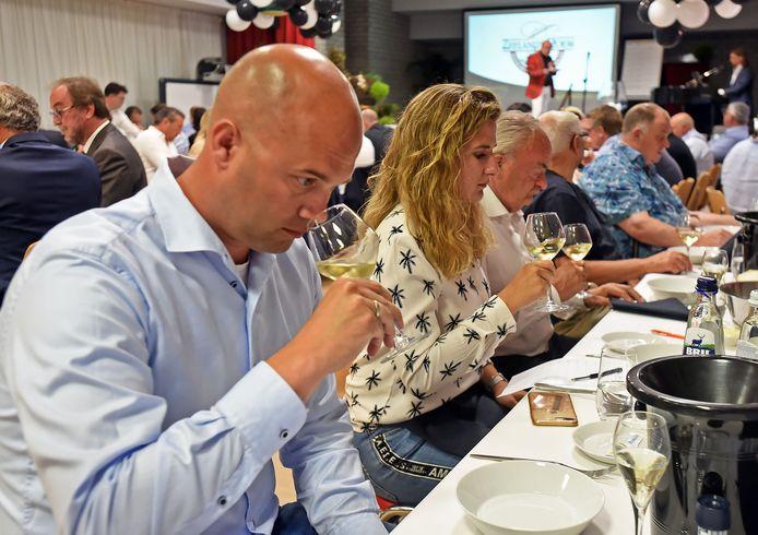 Verkiezing mosselwijn seizoen 2019-2020. Wesley Visser (voorgrond) uit Philippine ruikt de wijn voor hem op te drinken.