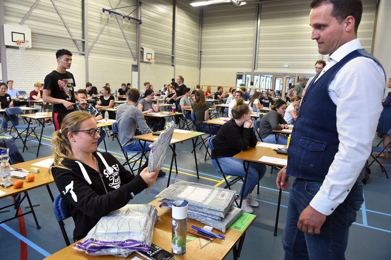Eindexamen wiskunde voor vwo op het dr Mollercollege te Waalwijk. Een leerlinge moet vooraf controleren of de verpakkingen om de examens wel goed dicht zitten.  Beeld Marcel van den Bergh / de Volkskrant