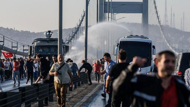 Oproerpolitie jaagt mensen met waterkanonnen van een brug over de Bosporus af. Beeld anp