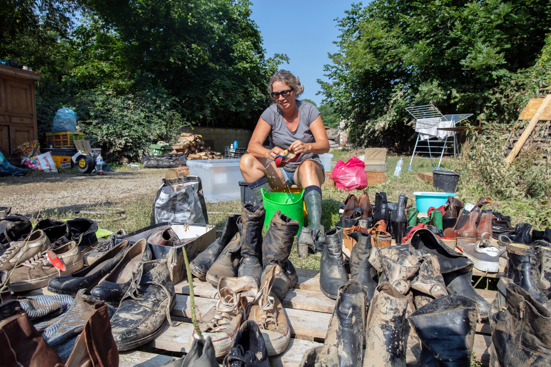 Een vrijwilliger helpt bij het schoonmaken van schoenen van een getroffen gezin. Beeld HJ Hunter