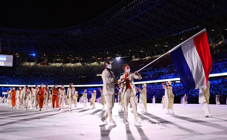 Keet Oldenbeuving en Churandy Martina dragen de Nederlandse vlag het olympisch stadion binnen.  Beeld Reuters