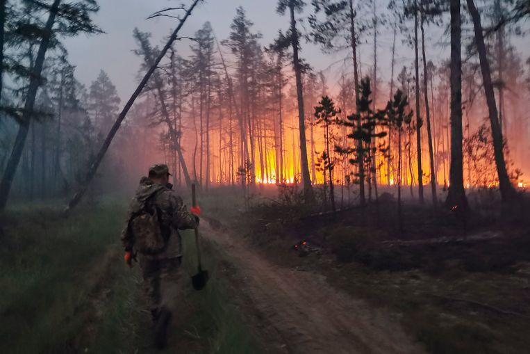 Een vrijwilliger gaat proberen een bosbrand te temperen in de Oost-Russische regio Jakoetië.  Beeld AP