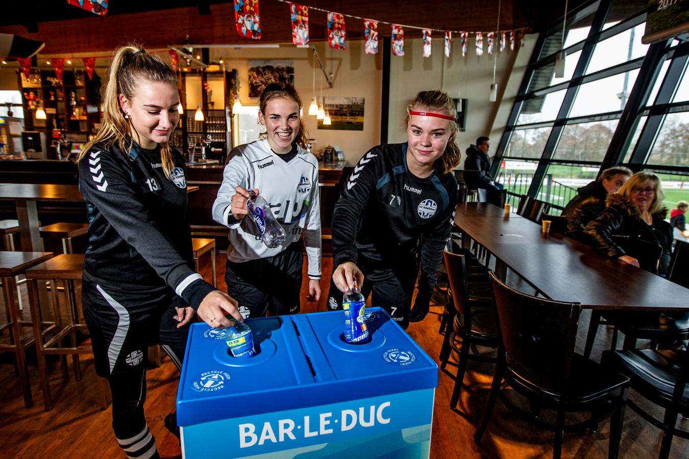 Lieselot van Slefhout (rode haarbandje) Meike Berning (witte shirt) en Isa van Dijck gooien een plastic flesje in een daarvoor bestemde plastic afvalbak, beschikbaar gesteld door Bar Le Duc.
