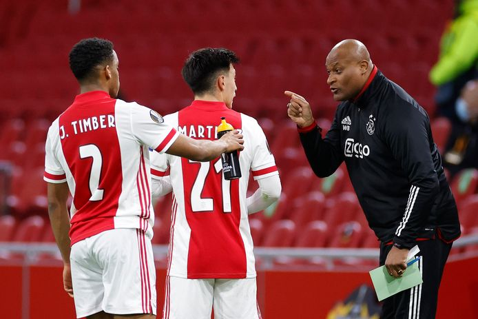 Winston Bogarde spreekt Ajax-spelers Jurien Timber en Lisandro Martinex vermanend toe.