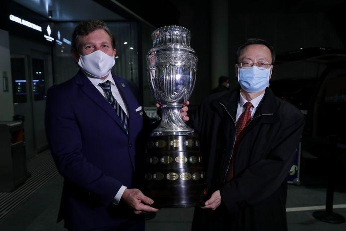 Voorzitter van de Zuid-Amerikaanse voetbalbond Alejandro Domínguez (links) en de Chinese ambassadeur in Uruguay Wang Gang, houden samen de trofee van de Copa América vast.