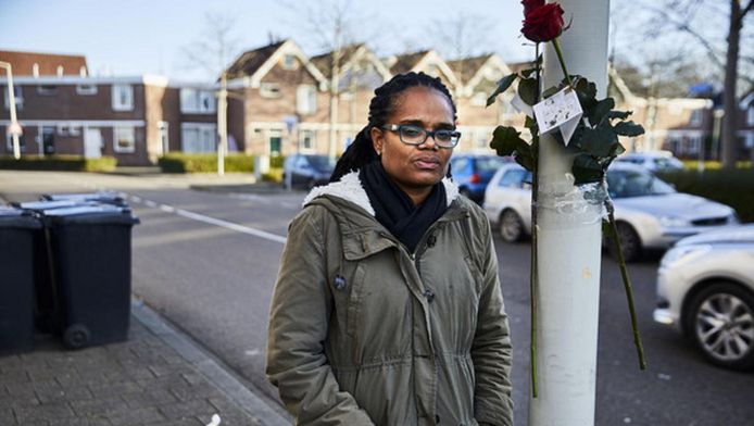 Luci Rimon in de straat op de plaats waar haar broer Shurandly en haar neefje Faichel gisteravond werden neergeschoten. Mensen hebben bloemen aan de lantaarnpaal gebonden.
