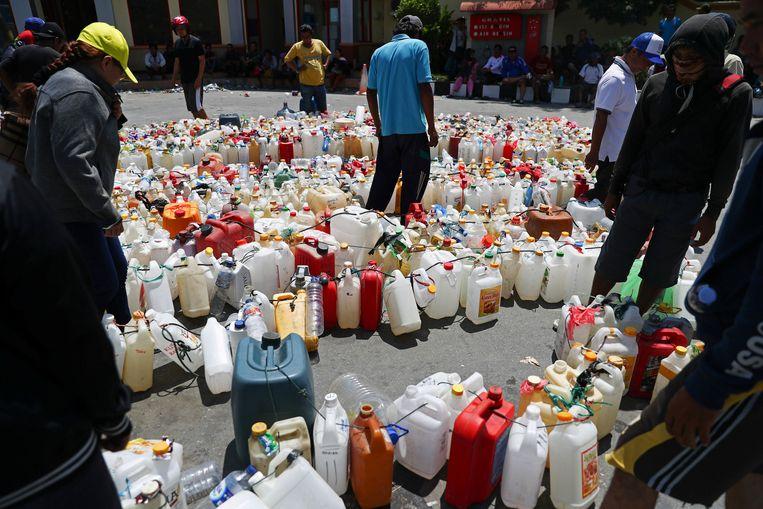 Overlevenden wachten tot het pompstation in Palu wordt bevoorraad. Zonder benzine voor hun brommers kunnen ze nergens eten halen. Beeld REUTERS