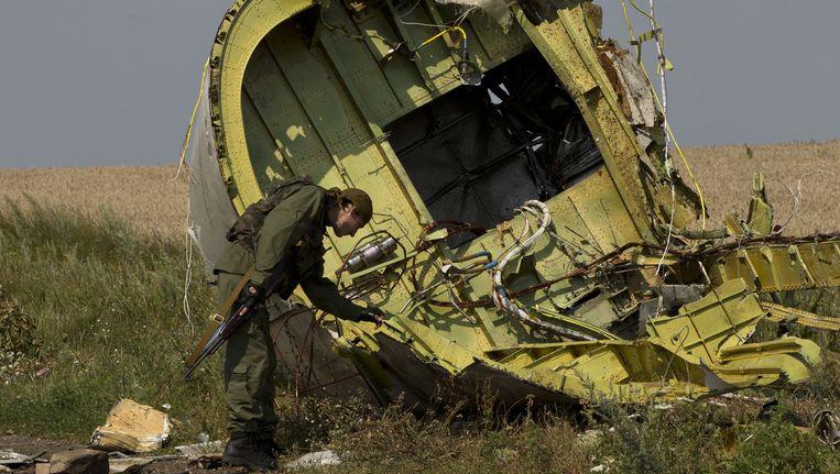 Een pro-Russische rebel raakt een wrakstuk van het neergestorte vliegtuig aan. Beeld ap