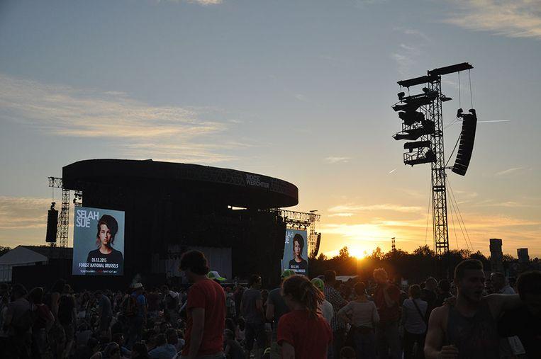 De zon gaat onder, terwijl op het hoofdpodium de komst van Faith No More wordt voorbereid. Beeld Astrid Snoeys