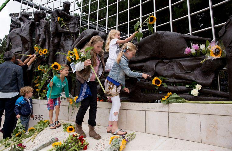 Kinderen leggen tijdens de herdenkingsplechtigheid zonnebloemen bij het Indisch Monument voor hun overgrootvader die in de oorlog overleden is. Met de capitulatie van Japan op 15 augustus 1945 kwam een einde aan de Tweede Wereldoorlog in Zuidoost-Azie.  Beeld Martijn Beekman / ANP