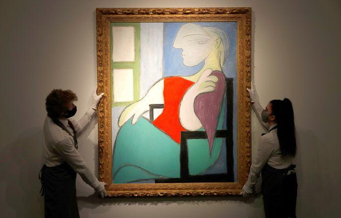 Medewerkers van veilinghuis Christie's tonen het schilderij 'Femme assise près d'une fenêtre (Marie-Thérèse)' van Pablo Picasso, dat donderdag in New York werd geveild voor zo'n 85 miljoen euro.