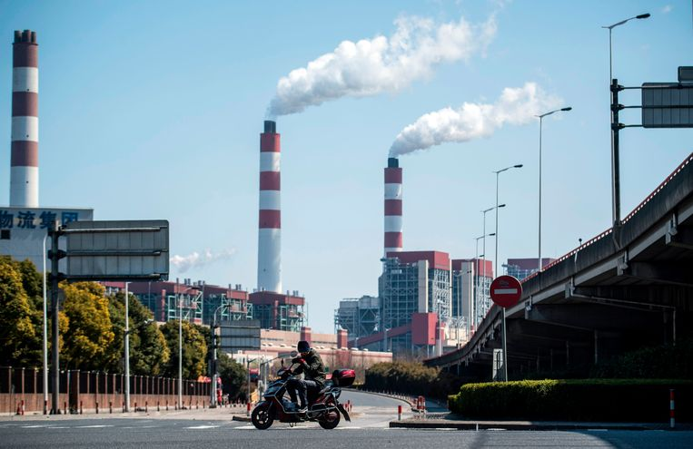 A man rides his scooter near a coal power plant in Shanghai. The gap is