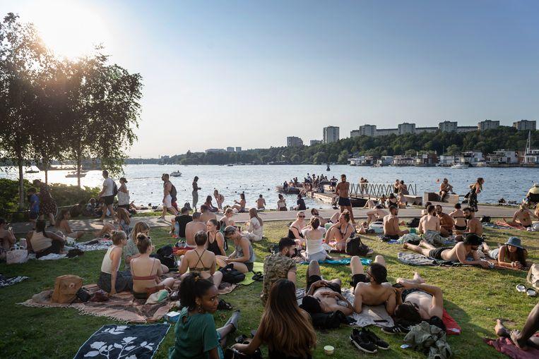 Mensen genieten van een zwoele avond in een park nabij Stockholm. Beeld EPA