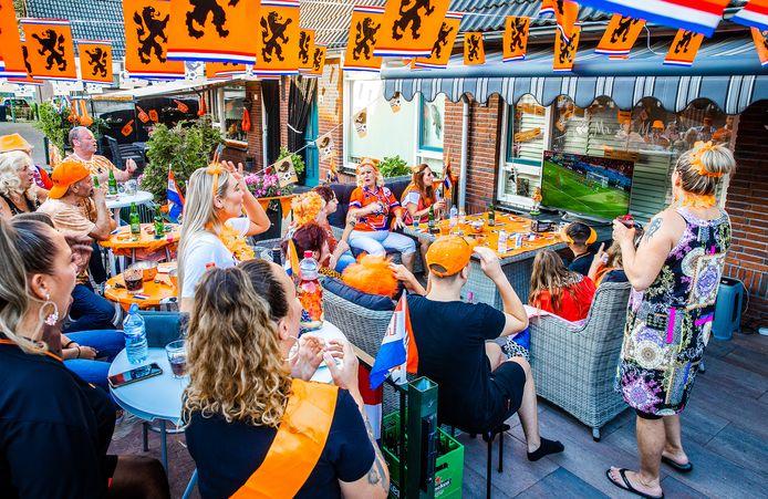 In Wielwijk kijken buurtbewoners in hun voortuinen naar de eerste poulewedstrijd van Nederland.