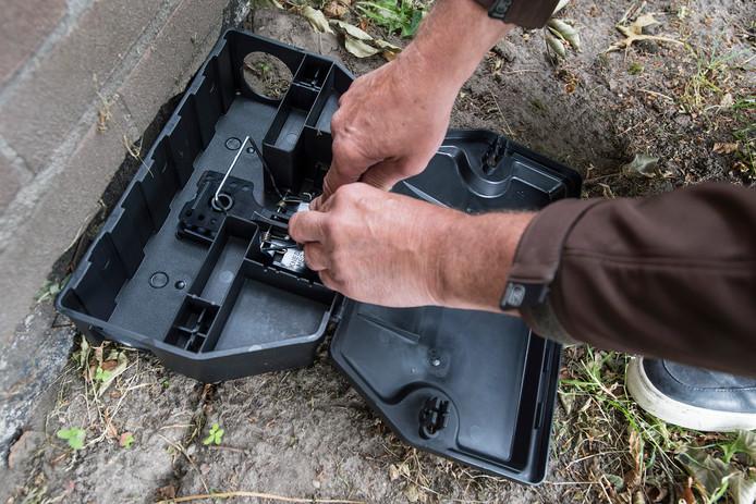 Een medewerker van de ongediertebestrijding zet een rattenval op scherp.