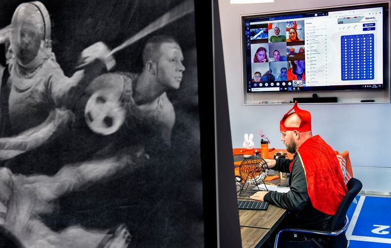 Hulpsinterklaas Niels van Huenen heeft samen met Sanne Vedder (niet zichtbaar) een virtuele Sinterklaasbingo georganiseerd waaraan 65 topsporters van Papendal via een beeldscherm (zichtbaar boven de mijter) deelnemen. Nog 228 dagen tot Tokio. Beeld Klaas Jan van der Weij