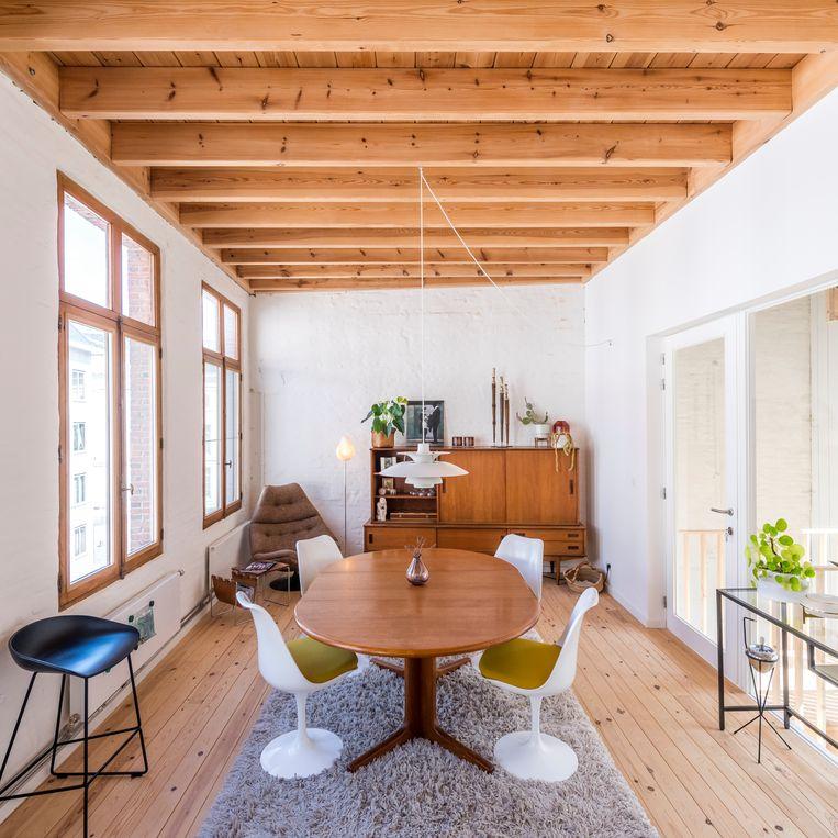 In de open leefkeuken met eethoek is het opnieuw vintage troef met de Tulip chairs van de Fins-Amerikaanse architect en ontwerper Eero Saarinen, een hanglamp van Louis Poulsen en een bruine Artifort-fauteuil.  Beeld Luc Roymans