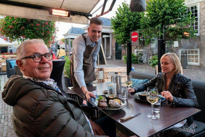 Eigenaar en gastheer Auke Rauwerda serveert een gerecht op het terras van In den Verdwaalde Koogel.