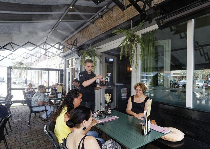 Gasten krijgen hun drankje geserveerd op het met waternevel gekoelde terras van Opa Pietje op het Mgr. Zwijsenplein in Kerkdriel.