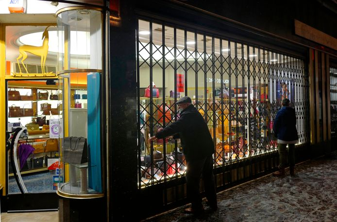 Een man in Lille (Rijsel) sluit zijn lederwarenwinkel, net voor het ingaan van de avondklok.